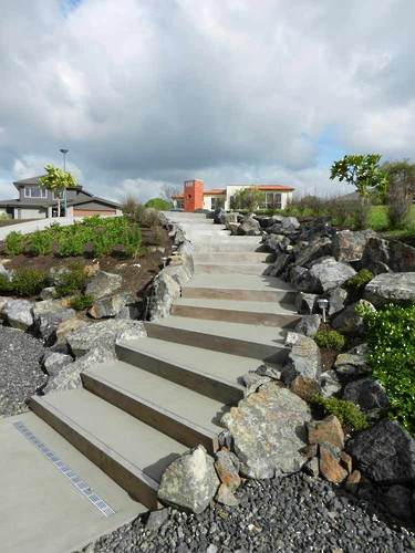 Blue-Stone-Retaining-Wall-with-Coloured-Concrete-Steps-Sweeping-Down-Steep-Bank-landscaping-ideas